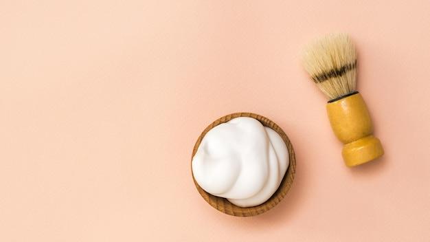 Pennello da barba e schiuma da barba in una ciotola di legno su uno sfondo di corallo. prodotti per la cura del viso da uomo.