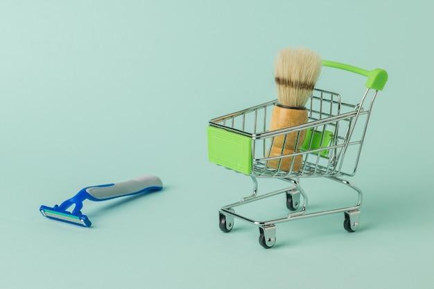 Un pennello da barba in un carrello della spesa e un rasoio usa e getta su una superficie blu