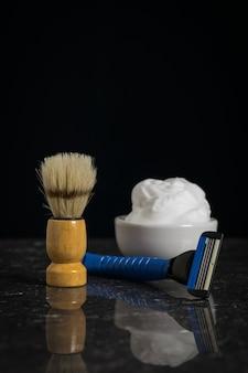Pennello da barba con schiuma e rasoio su una pietra su sfondo nero. set per la cura del viso di un uomo.