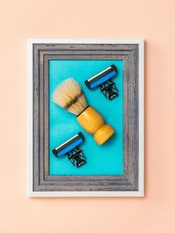 Pennello da barba con due lame intercambiabili in cornice su fondo corallo. collage. minimalismo. creatività creativa moderna.