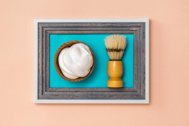 Pennello da barba in schiuma da barba e da barba in una cornice su uno sfondo di corallo. collage. minimalismo. creatività creativa moderna.