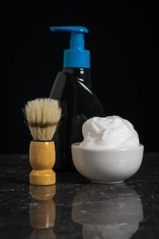 Schiuma da barba, gel detergente e pennello con setole rigide su fondo nero pietra. set per la cura del viso di un uomo.