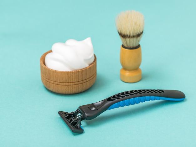 Macchina da barba con schiuma da barba e pennello su sfondo blu. set per la cura del viso di un uomo.