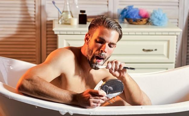 Rasatura uomo, barbiere e barbiere. ragazzo con rasoio, sapone, bagno. specchio gay nella vasca da bagno.