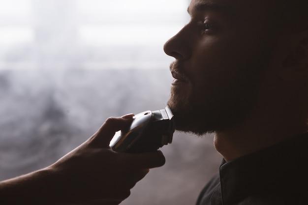 Primo piano alla moda dell'uomo di rasatura. contesto da barbiere. uomo alla moda a fuoco in primo piano, luogo suggestivo con fumo bianco, donna irriconoscibile con rasoio elettrico