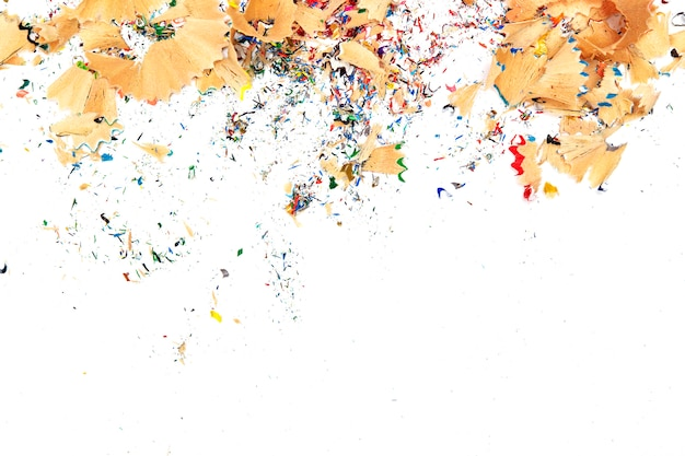 Trucioli dalle matite multicolori su fondo bianco