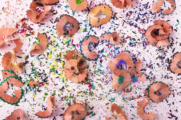 Trucioli di matite multicolori su sfondo bianco