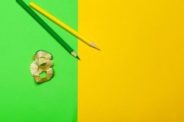 Trucioli di matite con carta su sfondo verde brillante