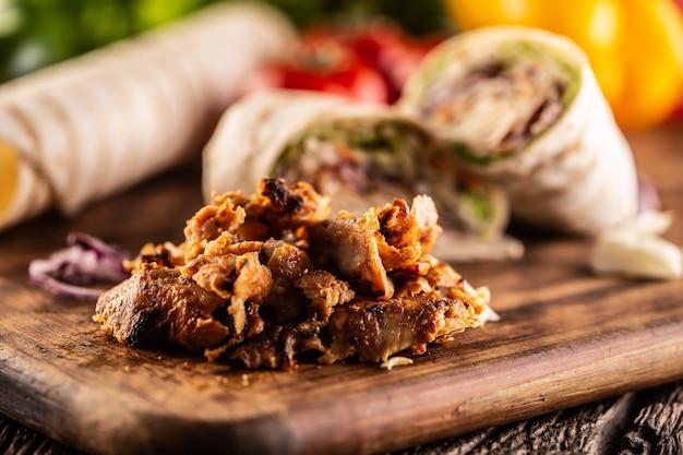 Trucioli di shawarma con tortillas ripiene in sottofondo.