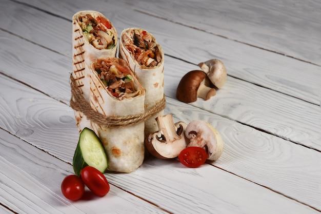 Shawarma doner kebab barbecue con verdure su fondo bianco in legno