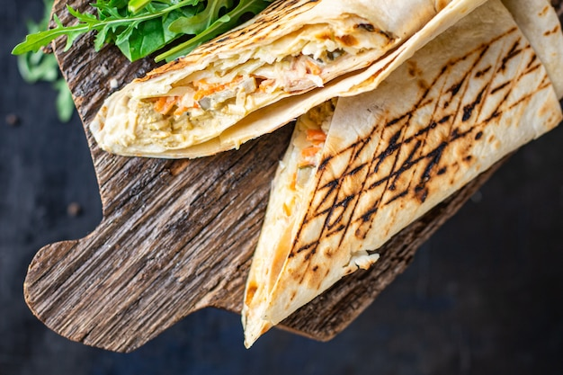 Shawarma doner kebab sandwich burrito carne verdura auce tacos cibo spuntino da asporto