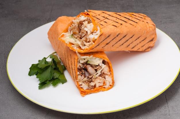Shawarma o doner kebab con pollo su un piatto bianco