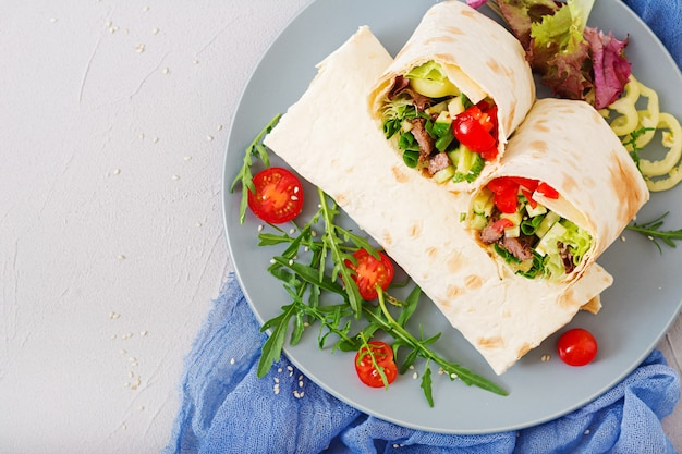 Shawarma di succosa carne di manzo, lattuga, pomodori, cetrioli, paprika e cipolla nel pane pita. menu dietetico. disteso. vista dall'alto