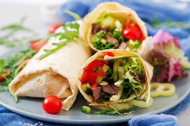 Shawarma di succosa carne di manzo, lattuga, pomodori, cetrioli, paprika e cipolla nel pane pita. menu dietetico.
