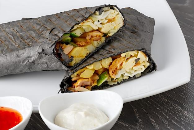 Shawarma in pane pita viene tagliato e si trova su un piatto bianco