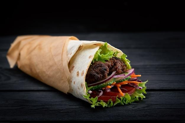 Shawarma arrotolato in lavash, carne alla griglia umida con cipolla, erbe e verdure su fondo di legno nero.