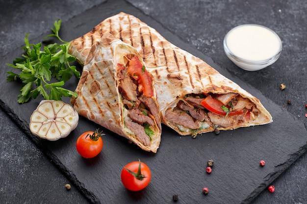 Shawarma con carne, spalla mancante, con salsa, pomodori, formaggio, erbe aromatiche e aglio, su ardesia nera, su sfondo nero