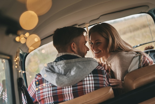 Lei è il centro del suo universo. bella giovane coppia sorridente mentre è seduta faccia a faccia sui sedili del passeggero anteriore in mini van in stile retrò