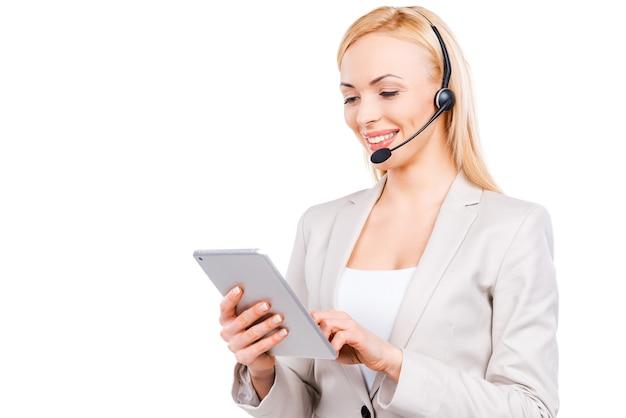 Lei sa come aiutarti. fiducioso rappresentante del servizio clienti maturo che lavora su tablet digitale e sorride mentre si trova in piedi su sfondo bianco