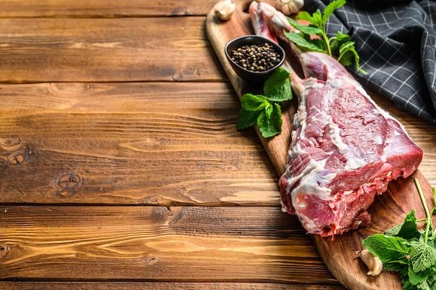 Pecora, coscia di agnello alle erbe. carne biologica cruda. fondo in legno. vista dall'alto. copia spazio.