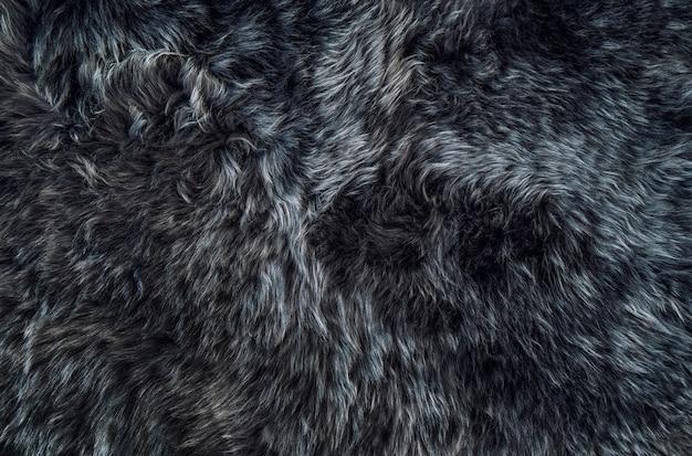 Trama di sfondo scuro tappeto di pelle di pecora pelliccia di pecora