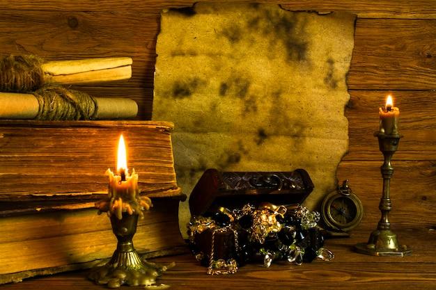 Un foglio di carta bruciata con spazio per testo, vecchi libri e pergamene, candele accese, uno scrigno del tesoro su uno sfondo di legno.