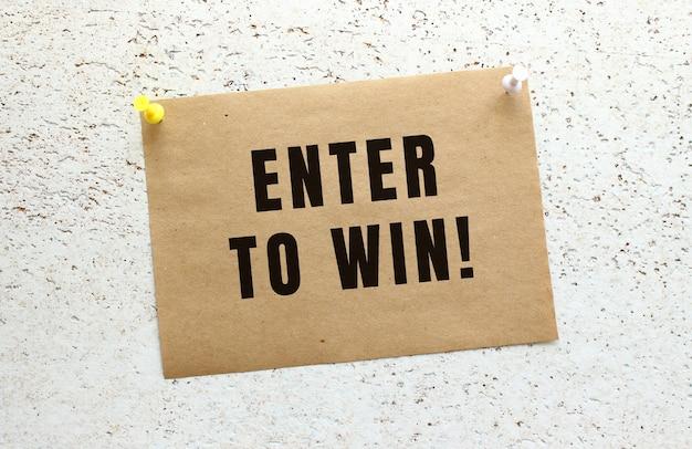 Un foglio di carta artigianale con il testo invio per vincere attaccato a un muro bianco strutturato con un pulsante