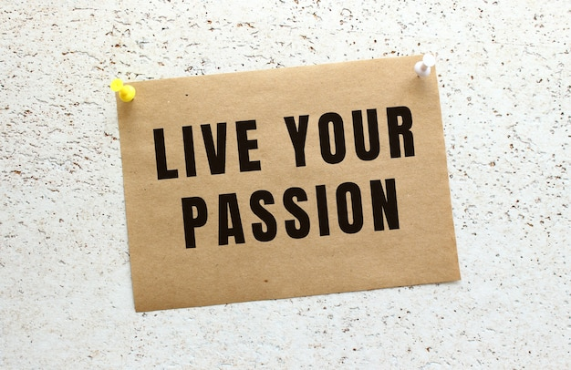 Un foglio di carta artigianale con il testo live your passion attaccato a un muro bianco strutturato con un pulsante. promemoria d'ufficio. concetto di affari.