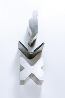 Strumento e attrezzatura di piegatura della lamiera sottile isolati su un fondo bianco. macchina piegatubi speciale formatura stampo punzone e matrice. utensili per pressa piegatrice, utensili per piegatura, punzone e matrice per pressa piegatrice.