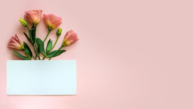 Foglio di carta e ramo di fiori, copia dello spazio. spazio vuoto per i saluti. focalizzazione morbida
