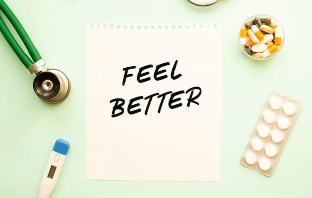 Un foglio di carta con testo sentire meglio, stetoscopio e farmaci. concetto medico.