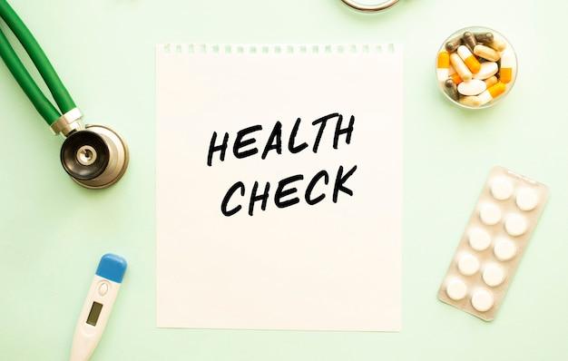Un foglio di carta con stetoscopio e farmaco del controllo di salute del testo