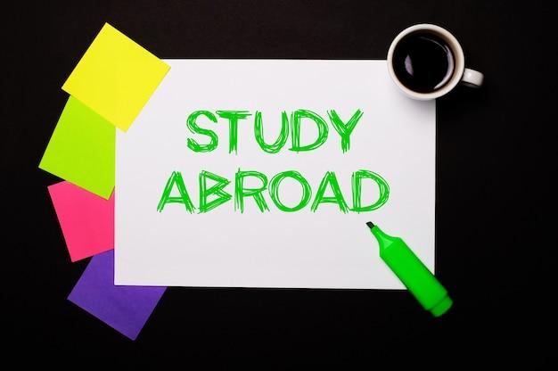 Un foglio di carta con le parole studio all'estero, una tazza di caffè, adesivi multicolori luminosi per appunti e un pennarello verde su una superficie nera
