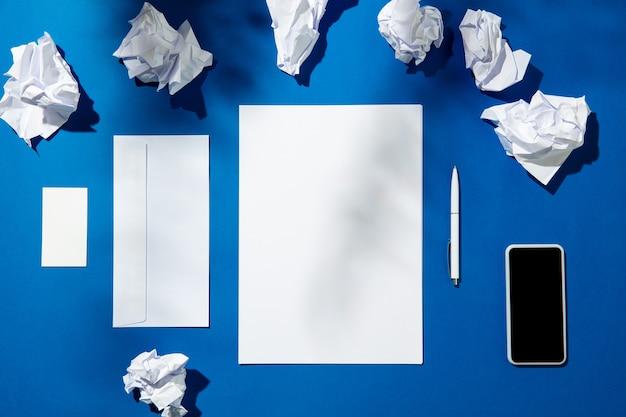Fogli, gadget e strumenti di lavoro su un tavolo blu per interni. luogo di lavoro creativo e accogliente in ufficio a casa, modello ispiratore con ombre di piante sulla superficie. concetto di ufficio remoto, freelance, atmosfera.