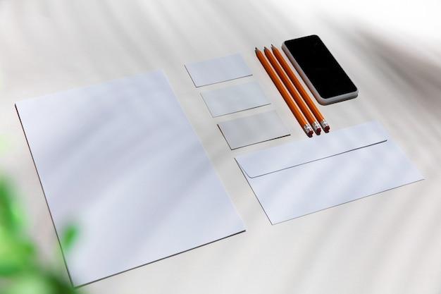 Fogli, gadget e strumenti di lavoro su un tavolo bianco per interni. luogo di lavoro creativo e accogliente in ufficio a casa, modello ispiratore con ombre di piante sulla superficie. concetto di ufficio remoto, freelance, atmosfera.