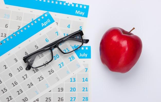 Fogli di calendario mensile, bicchieri, mela rossa su fondo bianco