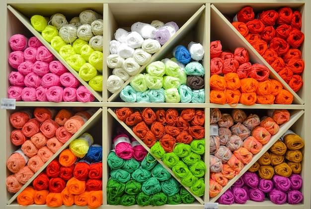 Mensola con palline di filato di lana di colori colorati sul banco di mostra del negozio in vendita