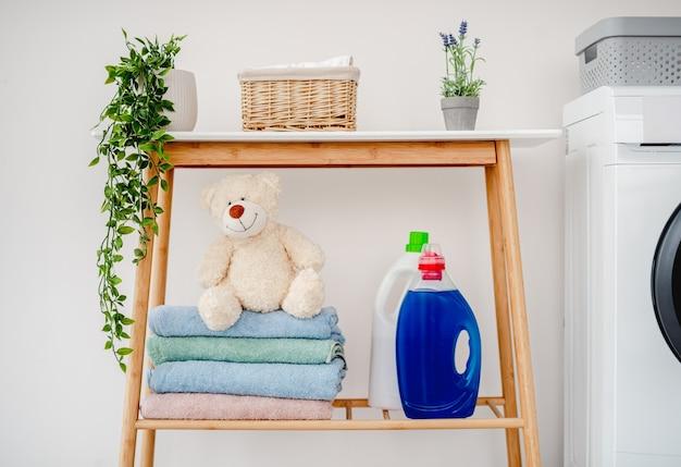 Mensola con detersivi in polvere, asciugamani puliti e peluche in piedi vicino alla lavatrice in una stanza luminosa