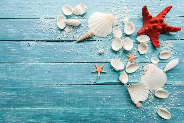 Conchiglie, sabbia e stelle su una superficie di legno blu