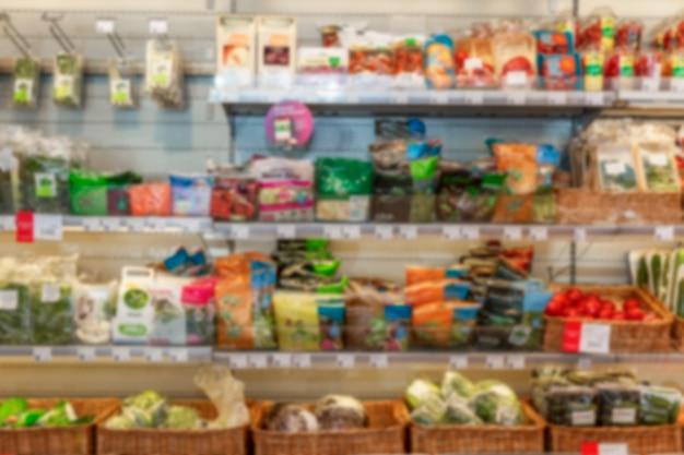 Scaffali con una varietà di verdure in un supermercato. vista frontale. sfocato.