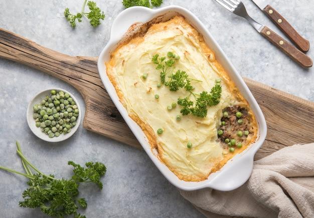 Torta di pastore con carne macinata di manzo, patate e formaggio su sfondo di legno, vista dall'alto, copia dello spazio. casseruola irlandese fatta in casa tradizionale