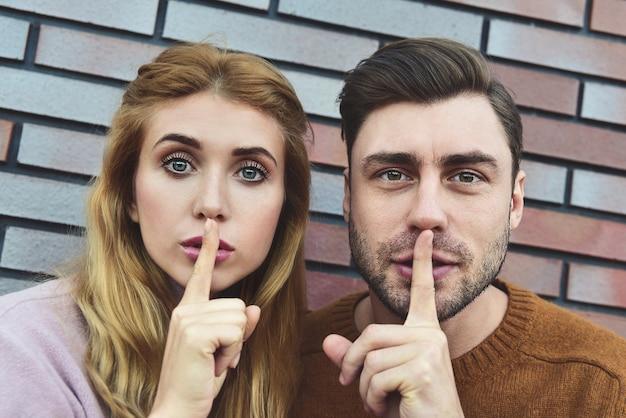 Shh, non dire a nessuno queste informazioni private. le coppie caucasiche sorprese fanno il gesto di silenzio con espressioni sorprese, chiedono di non diffondere pettegolezzi sui colleghi, isolati su sfondo di mattoni.