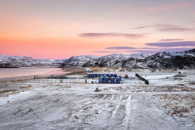 Campo di spostamento nell'artico, case sulla riva del mare di barents