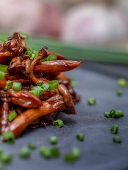 Fungo shimeji servito con erba cipollina su lastra di pietra nera. piatto tipico orientale. dettaglio del piatto di cibo, primo piano, messa a fuoco selettiva.