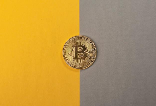 Moneta bitcoin brillante sul tavolo giallo e grigio alla moda.