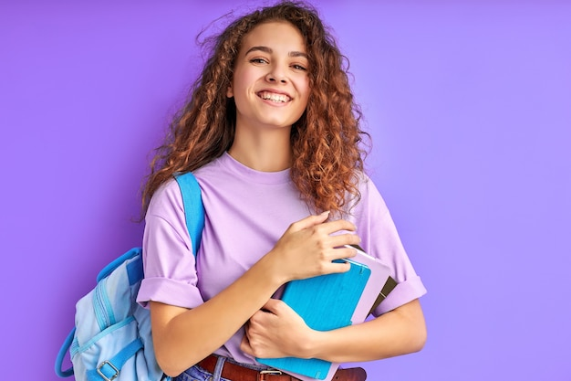Brillante di felicità studentessa isolata su sfondo viola, ama studiare
