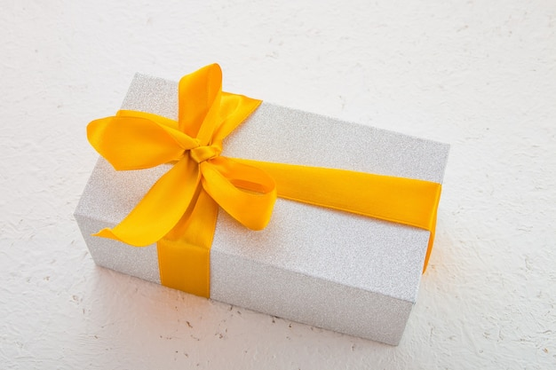 Confezione regalo lucida con fiocco oro su sfondo bianco