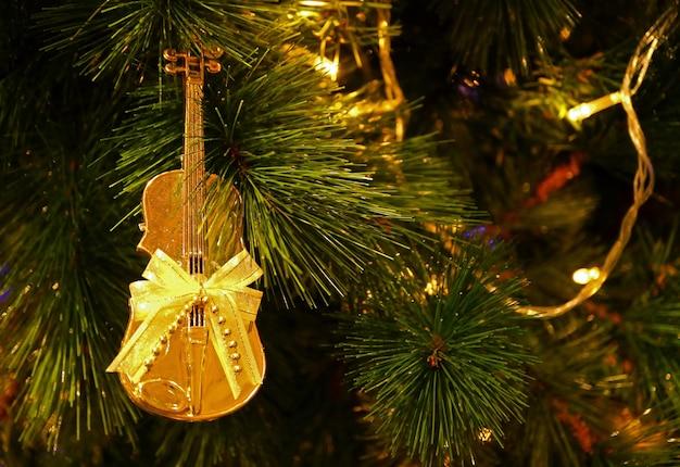 Violoncello oro lucido a forma di con fiocco in nastro ornamento di natale appeso all'albero di natale