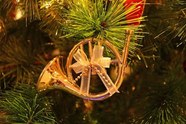 Oro lucido a forma di corno francese con fiocco in nastro ornamento di natale appeso all'albero di natale