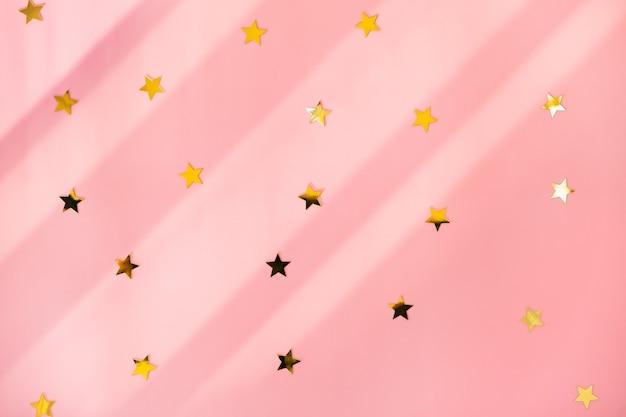 Stelle dorate lucide sulla superficie rosa